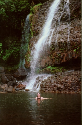 Stasha swimming under a waterfall in Kauai
