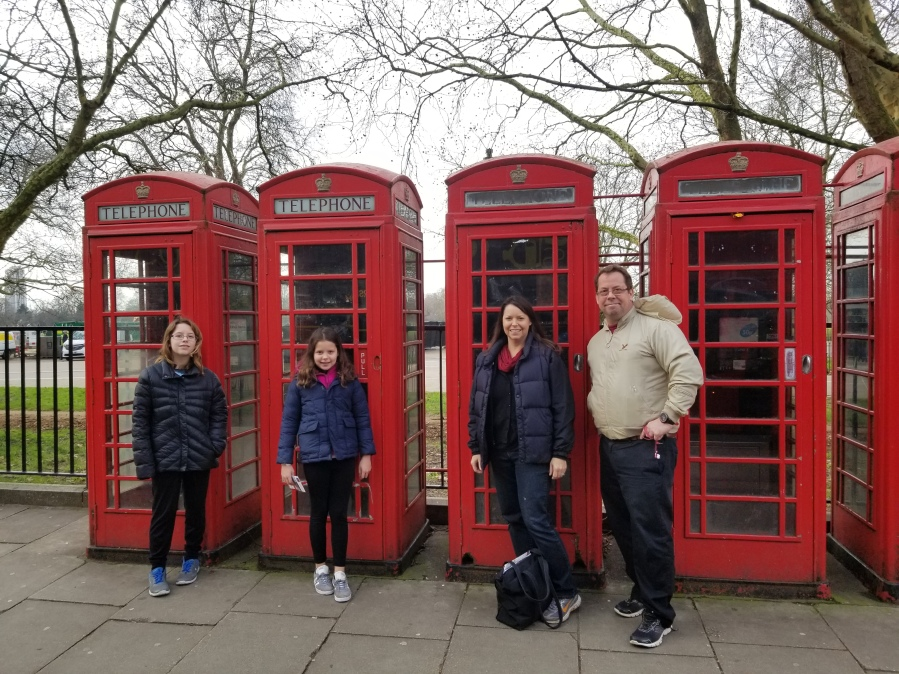 Family in front of red British phone booths in London. Photo by Anastasia Mills Healy.
