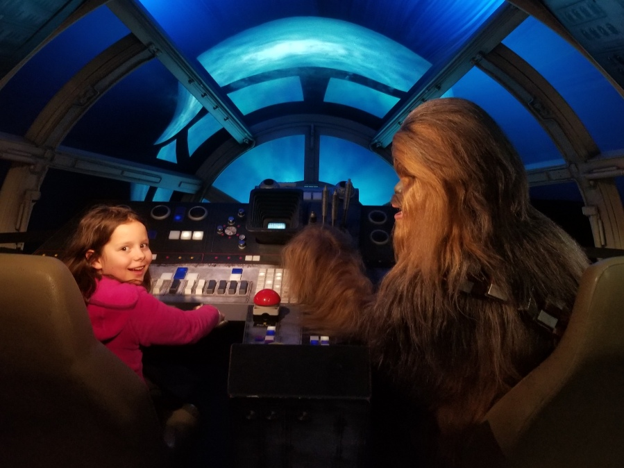 Child in the Millennium Falcon cockpit with Chewbacca at Madame Tussaud's London's Star Wars exhibition. Photo by Anastasia Mills Healy.