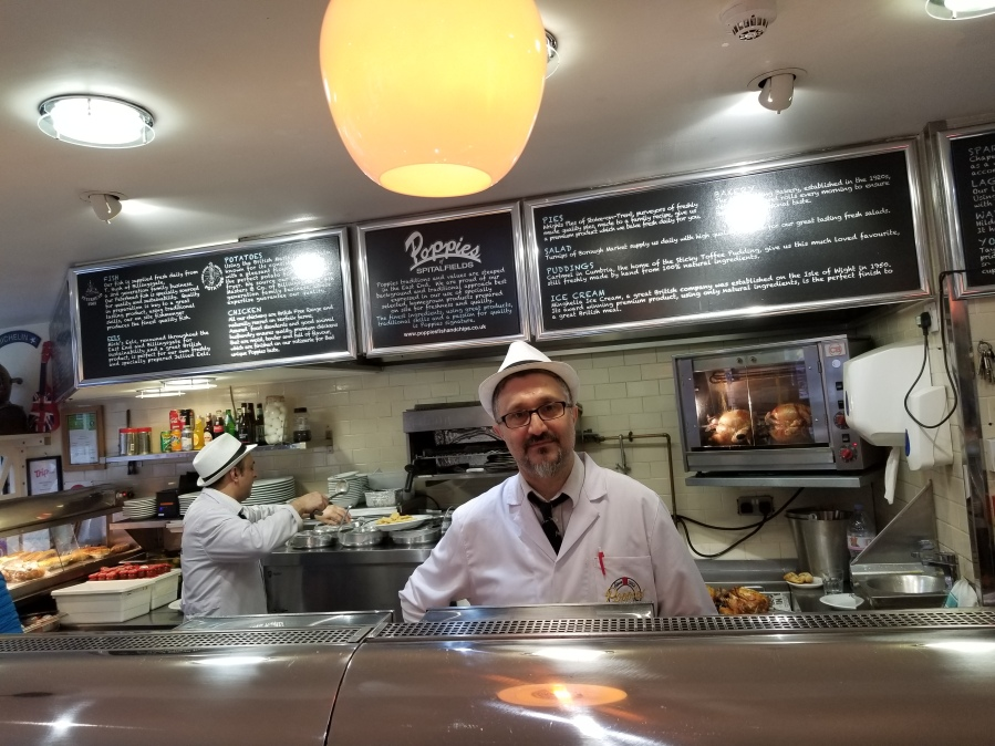 Counter service worker at Poppies, London, lauded as serving the city's best fish and chips. Photo by Anastasia Mills Healy, taken on an Eating Europe food walking tour.
